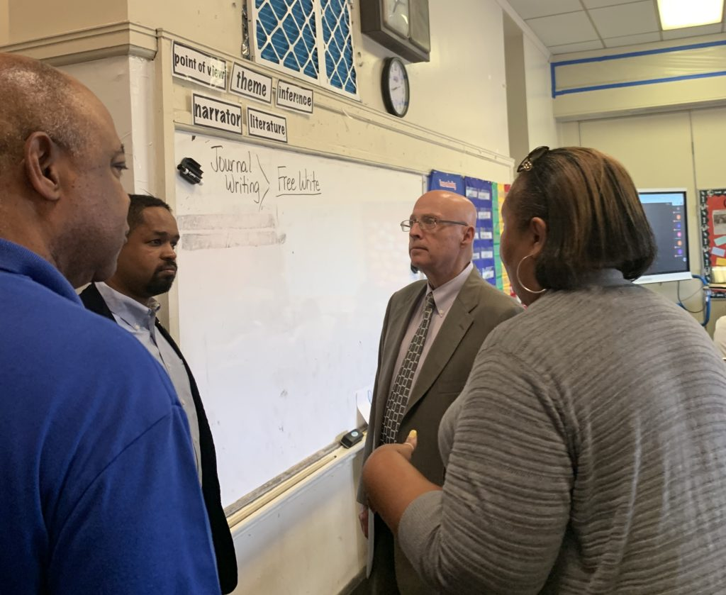 (l to r:) Jerry Jordan, Sharif Street and Arthur Steinberg talk with a PFT member about the impact of lead abatement efforts on her classroom