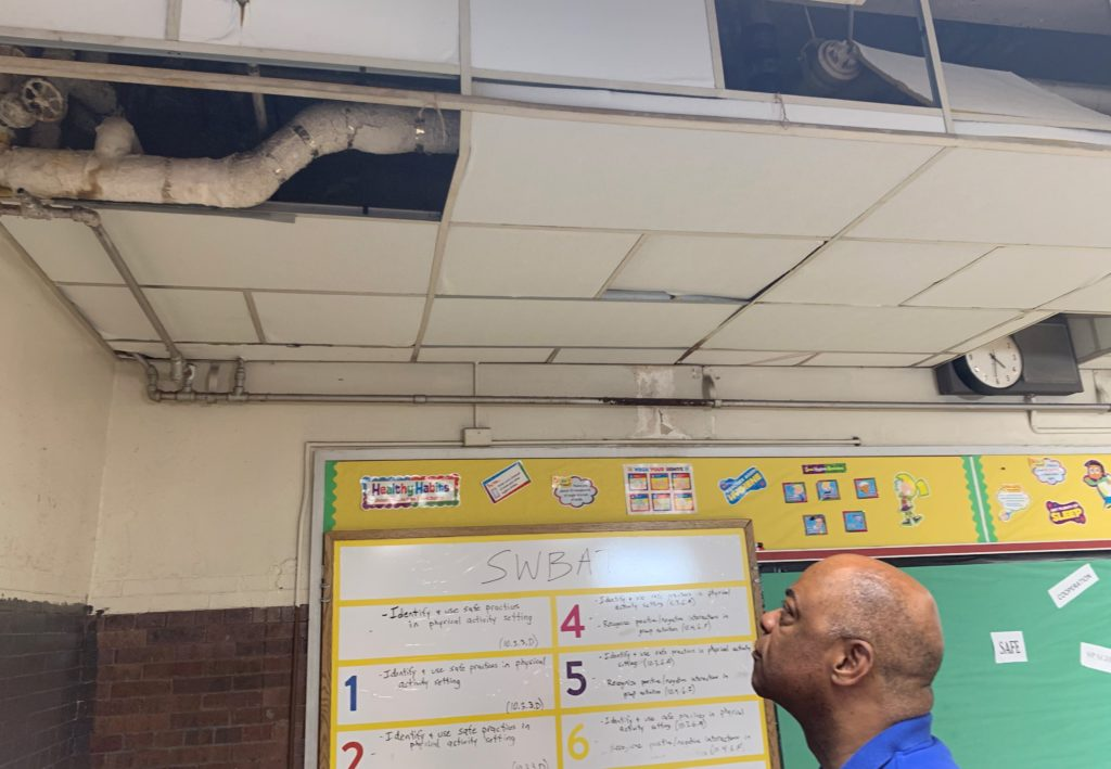 PFT President Jerry Jordan views exposed and damaged asbestos pipe in the school's gym the